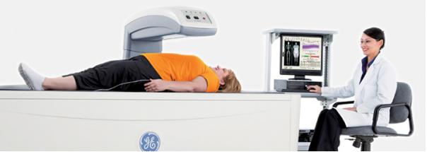 Woman in bright orange shirt laying on DEXA machine as doctor operates mechanics via computer