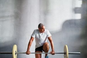 Mature man preparing to lift weighted barbell