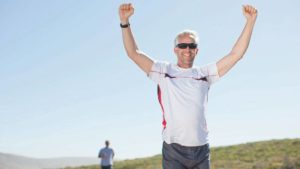 A middle-aged man outside jogging with arms raised and smiling as if celebrating