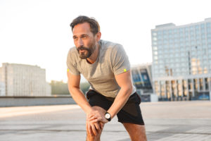Mature man stretching before jogging in urban area