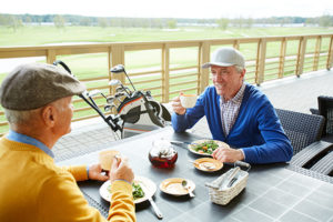 mature gentlemen eating salads after playing golf during vacation