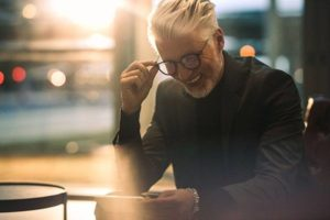 Mature business man putting on glasses in building while smiling at phone