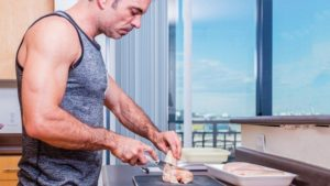 Muscular middle-aged man in blue tank in kitchen cutting up a chicken breast